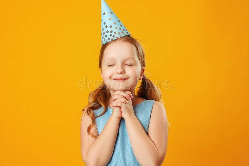 Cute little girl celebrates birthday. The child closed his eyes and made a wish. Closeup portrait on yellow background stock photography