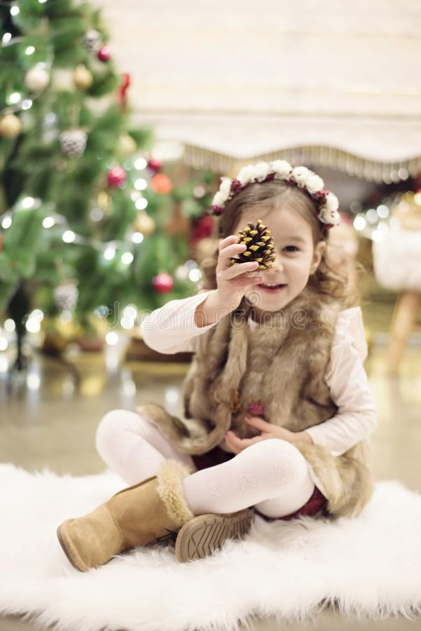 Cute little girl celebrating Christmas at home. She sits on a chair and holds a spruce cone in her hands. Positive emotions. Christmas tree in background stock photo