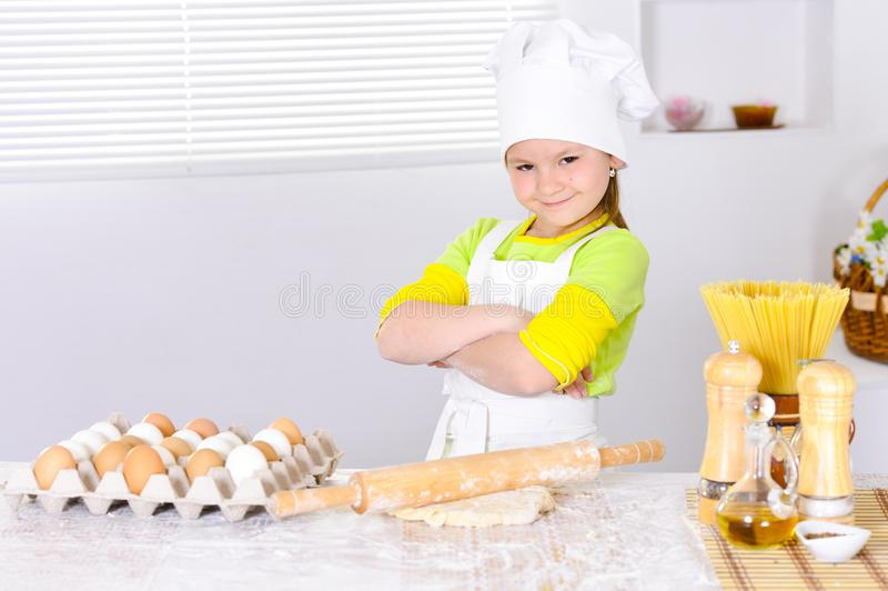 Cute little girl in chef`s hat baking cake in the kitchen stock photography