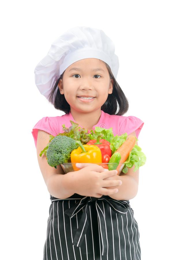 Cute little girl chef with vegetables stock image
