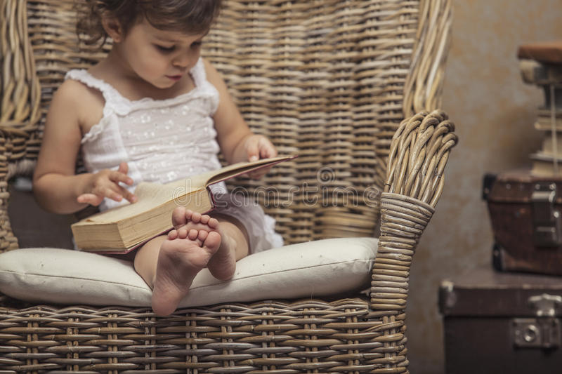 Cute little girl child in a chair, reading a book in interior stock image