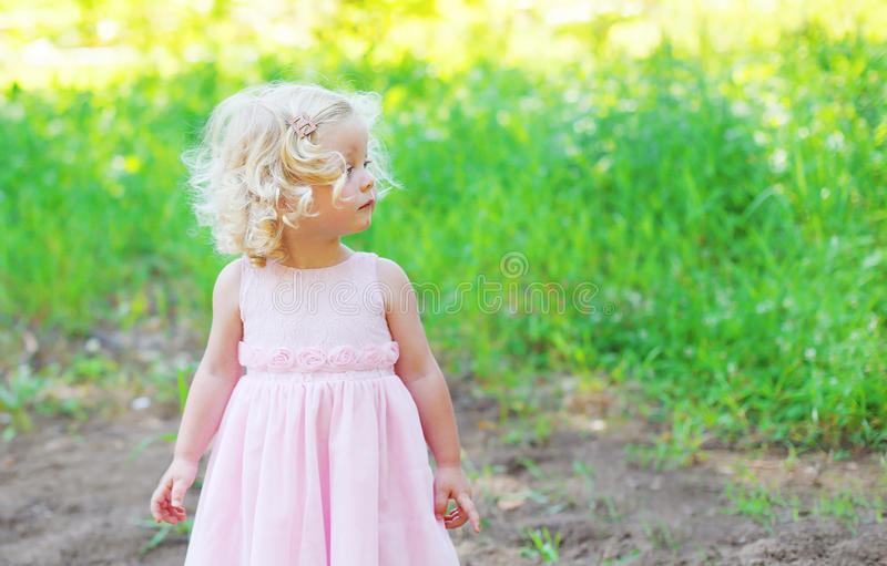 Cute little girl child with curly hair wearing a pink dress. In profile over summer background stock photo