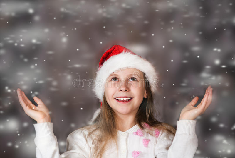 Cute little girl in a Christmas hat enjoys the falling snow royalty free stock images
