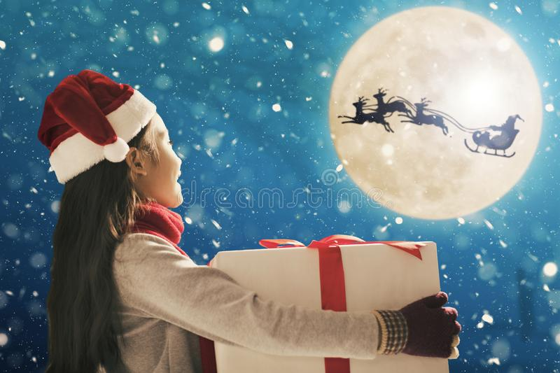 Cute little girl with christmas presents. Santa Claus flying in  moon sky royalty free stock photos