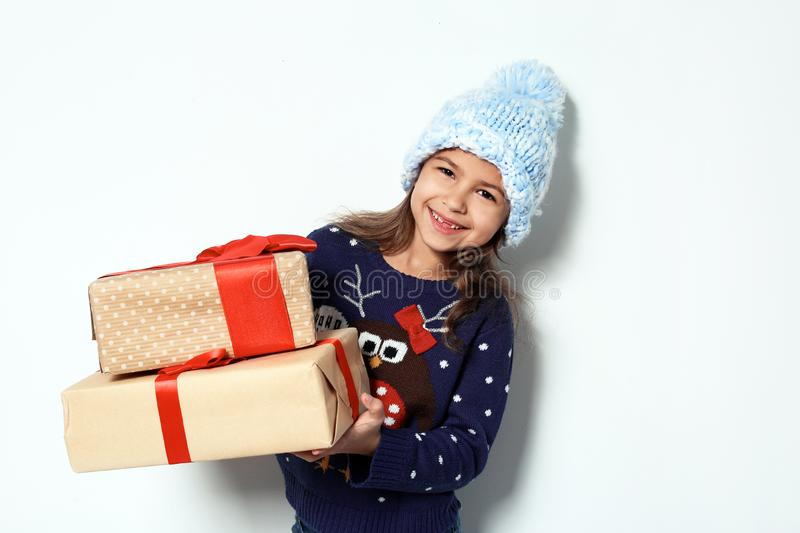Cute little girl in Christmas sweater and knitted hat holding gifts. On white background stock photos