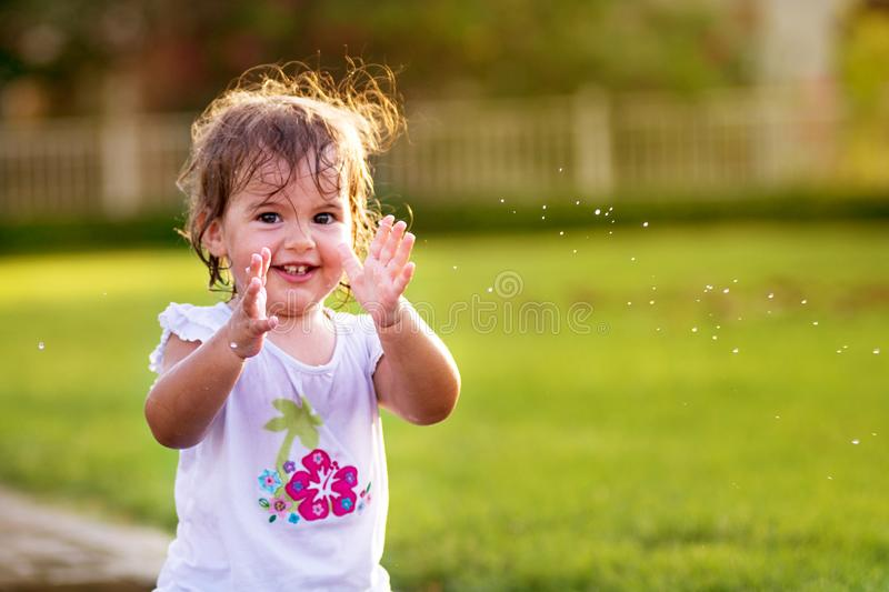 Cute little girl clapping her hands stock images