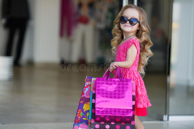 Cute little girl with colorful bags for shopping in supermarket. Beautiful little girl with blond long curly hair,sunglasses with glass in the form of hearts,in royalty free stock image