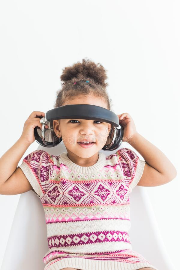 Cute little girl in a colorful dress listening to music with headphones on a white background stock photos
