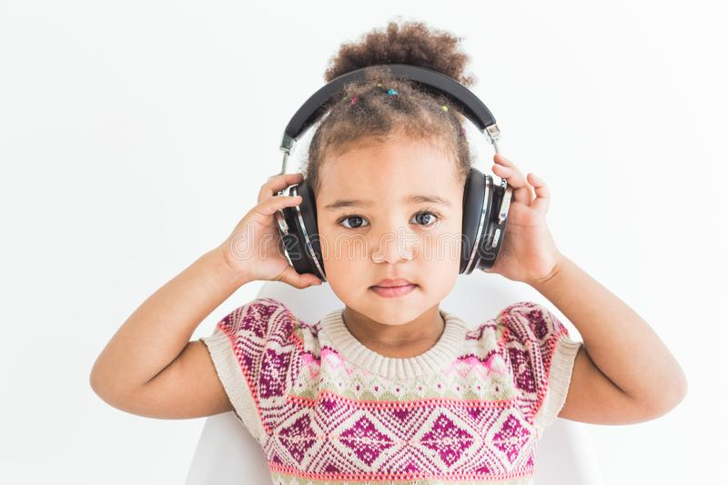 Cute little girl in a colorful dress listening to music with headphones on a white background stock images