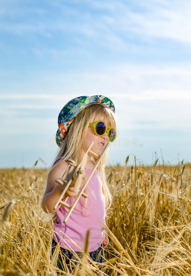 Cute little girl in a colorful hat and sunglasses stock photo