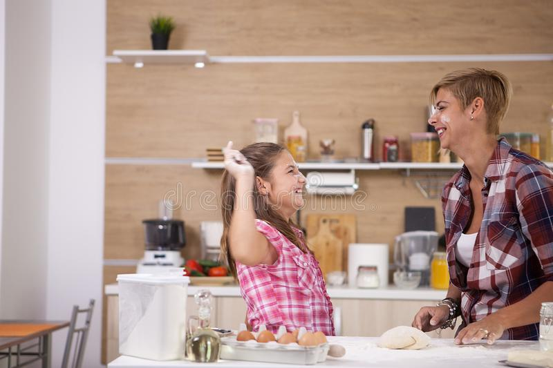 Cute little girl cooking with her mother healthy food stock image