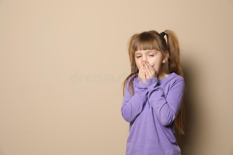 Cute little girl coughing against color background. Space for text stock images