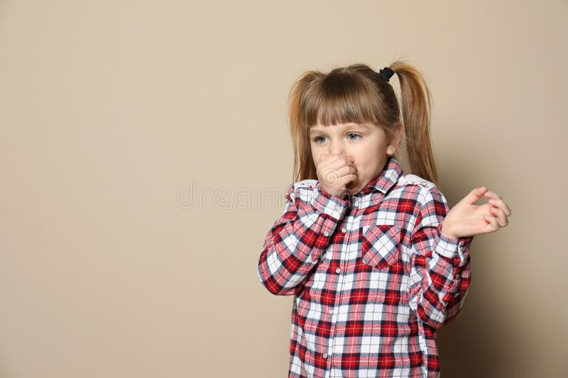 Cute little girl coughing against color background. Space for text royalty free stock photos