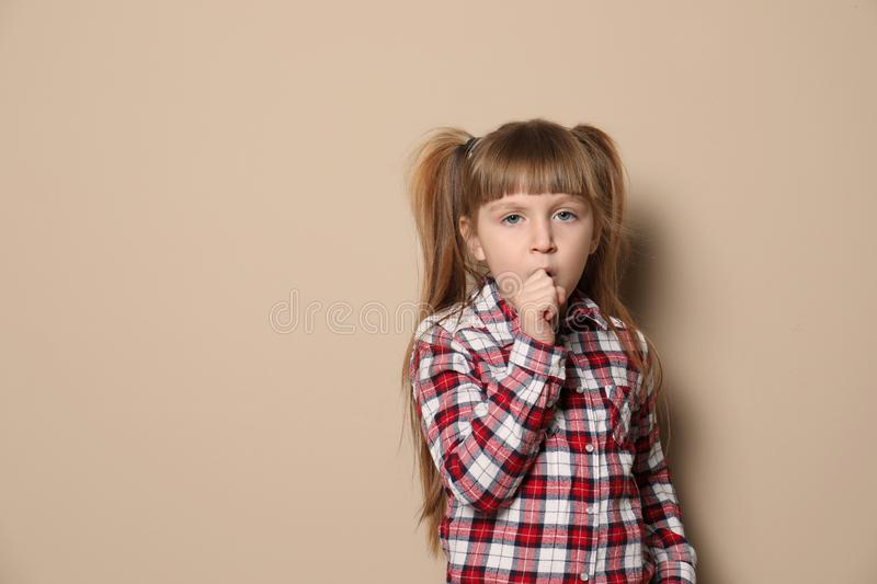 Cute little girl coughing against color background. Space for text royalty free stock photo