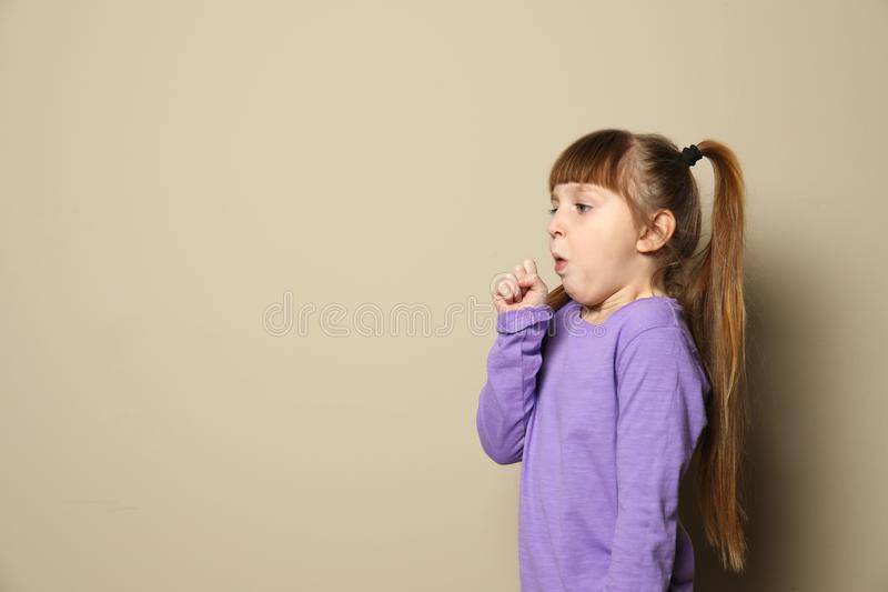 Cute little girl coughing against color background. Space for text stock photo