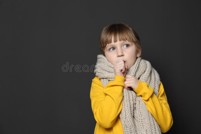 Cute little girl coughing against dark background. Space for text stock photos