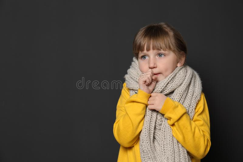 Cute little girl coughing against dark background. Space for text royalty free stock photo