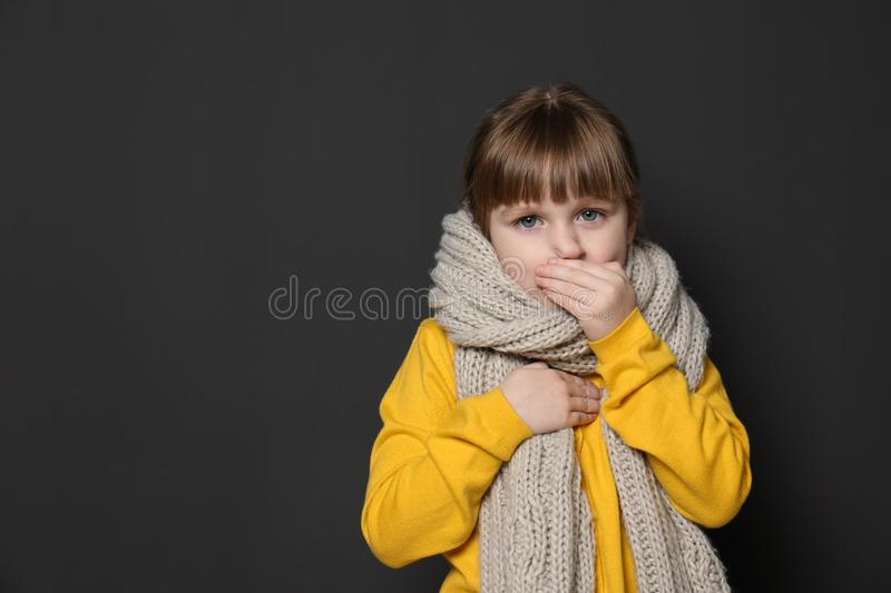Cute little girl coughing against dark background. Space for text royalty free stock photography