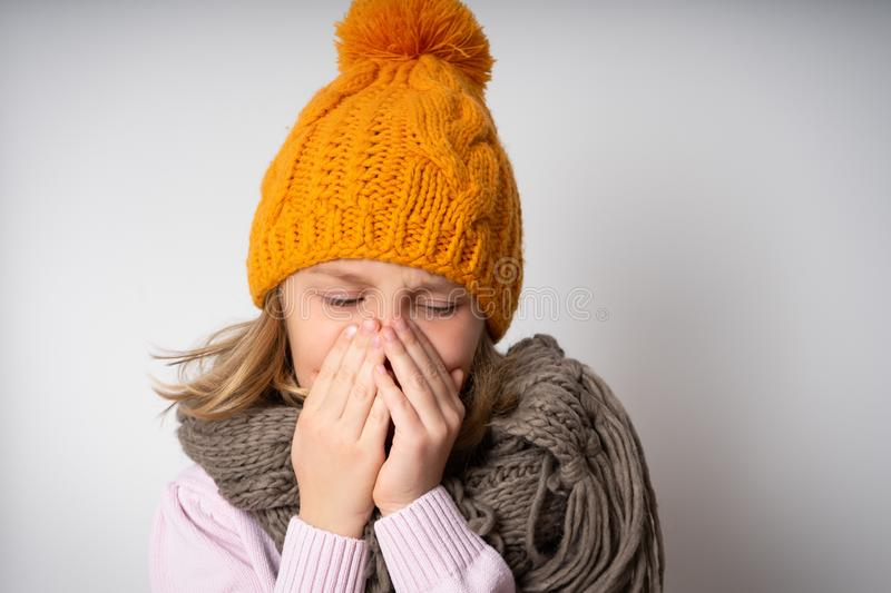 Cute little girl is coughing, on gray background royalty free stock photo
