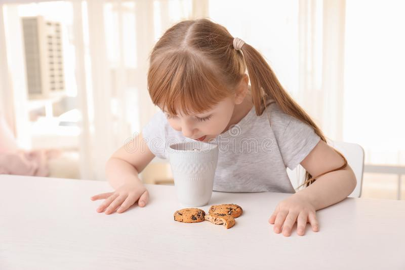 Cute little girl with cup of hot cocoa drink and cookies at home royalty free stock photos