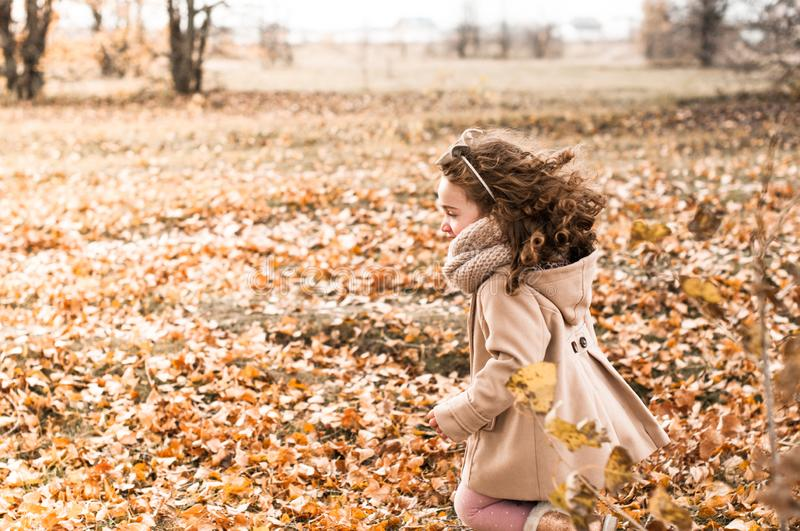 Cute little girl with curly hair rejoices in autumn,. Running through the fallen leaves stock images