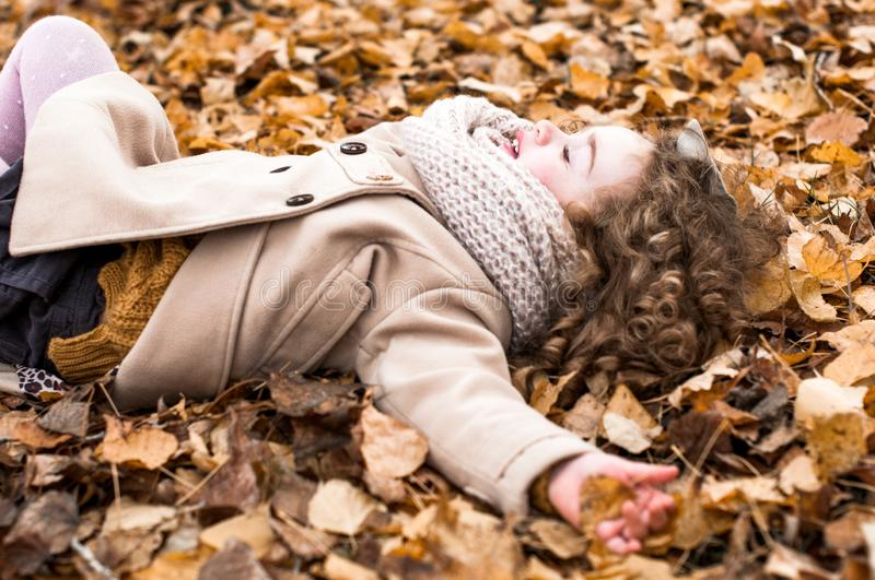Cute little girl with curly hair rejoices in autumn. Lies with eyes closed in fallen leaves stock photos