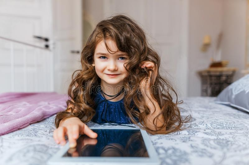 Cute little girl with curly hair using digital tablet royalty free stock photos