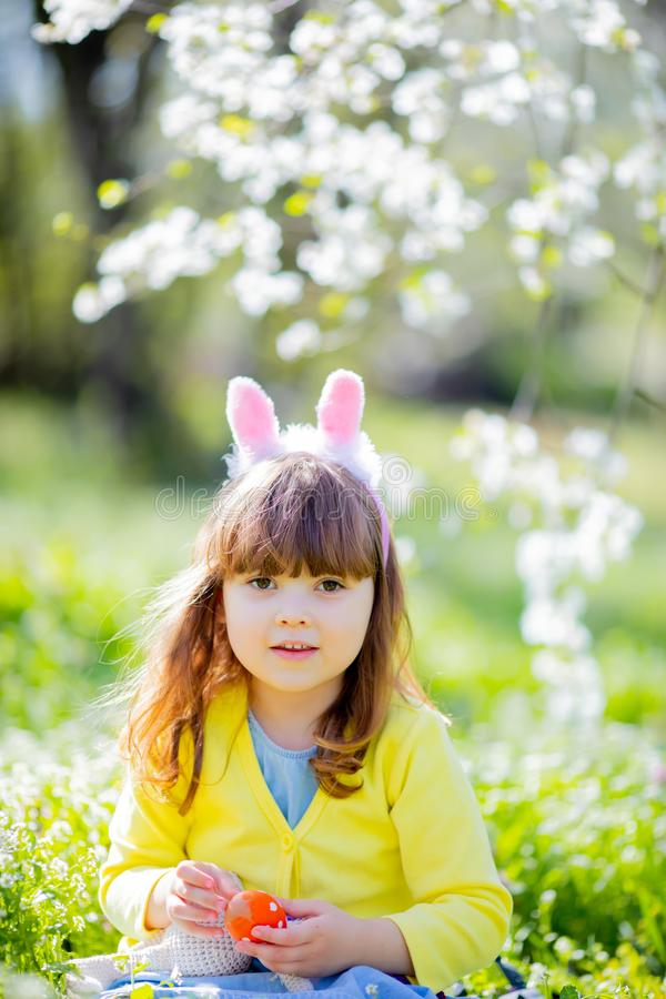 Cute little girl with curly hair wearing bunny ears and summer dress having fun during Easter egg hunt relaxing in the garden stock photo