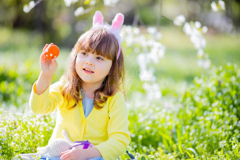 Cute little girl with curly hair wearing bunny ears and summer dress having fun during Easter egg hunt relaxing in the garden royalty free stock image
