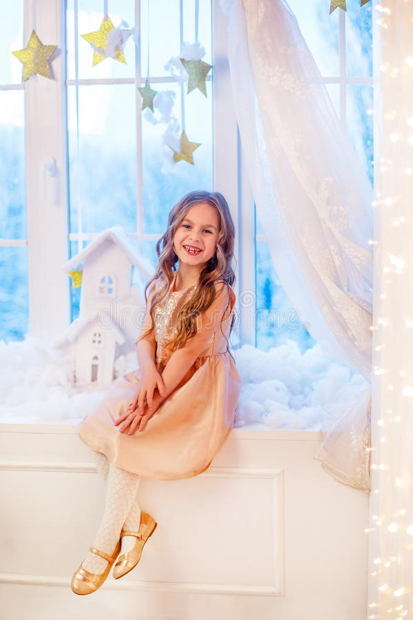 Cute little girl with curly hair at the window in anticipation of Christmas and New Year`s magic. Funny emotions in winter day stock image