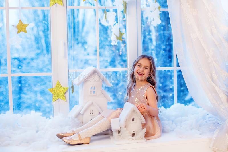 Cute little girl with curly hair at the window in anticipation of Christmas and New Year`s magic. Funny emotions in winter day stock photography