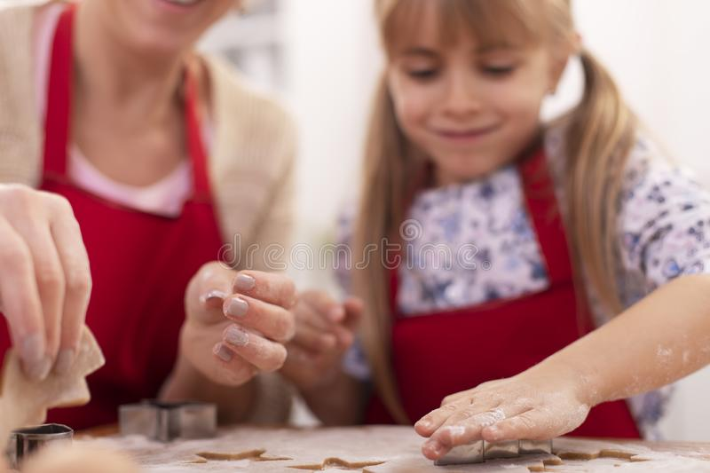 Cute little girl cutting gingerbread cookies from the stretched dough - her mother assisting and helping stock photography