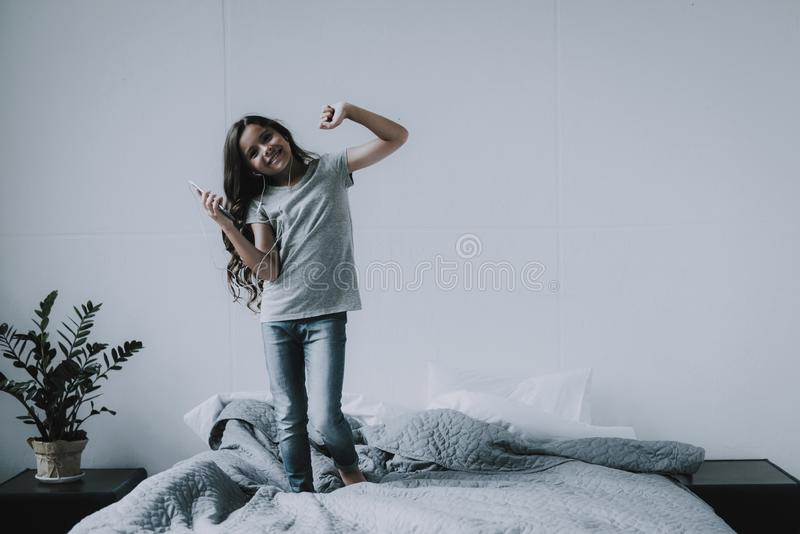 Cute Little Girl Dancing on Bed with Smartphone stock photo