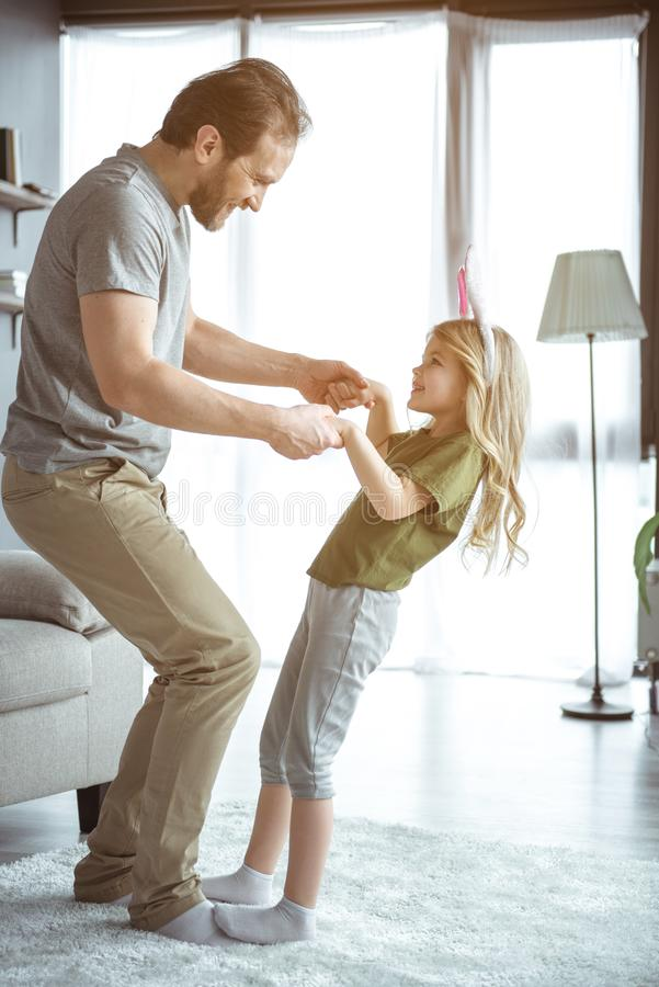 Happy father and daughter moving with joy in living room stock photo