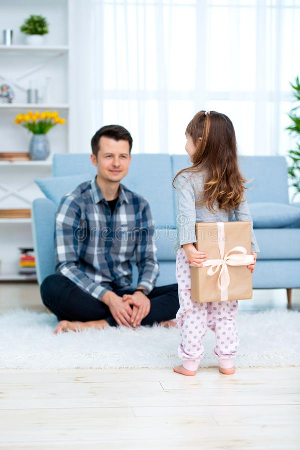 Cute little girl, daughter, sister gives a gift box to young dad father or brother. Both are smiling. Father`s day holiday concep royalty free stock photos
