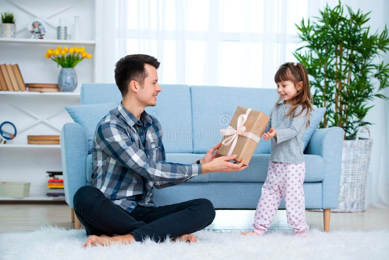 Cute little girl, daughter, sister gives a gift box to young dad father or brother. Both are smiling. Father`s day holiday concep stock photos