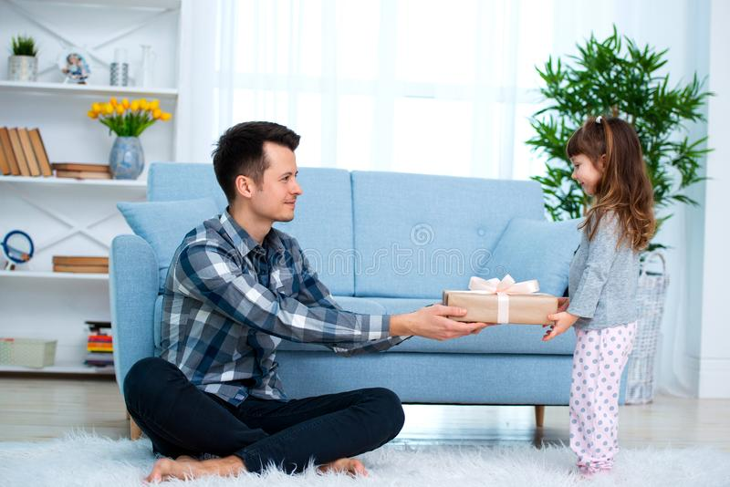 Cute little girl, daughter, sister gives a gift box to young dad father or brother. Both are smiling. Father`s day holiday concep stock photography