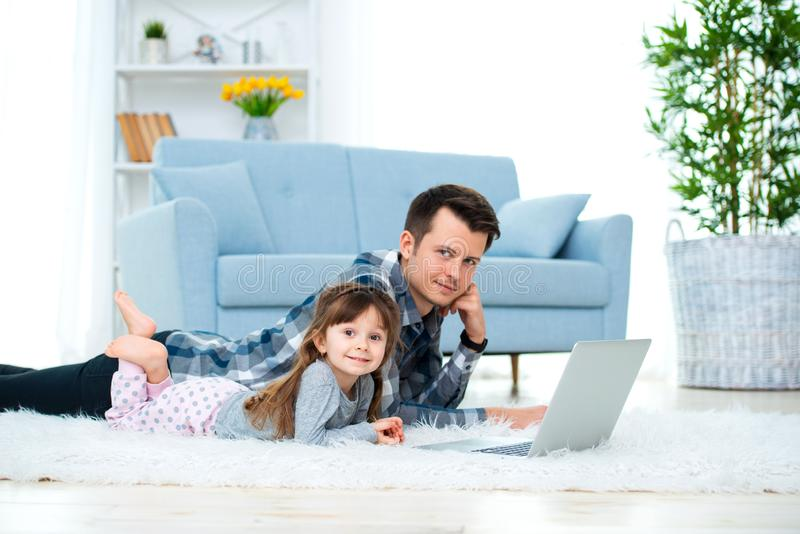 Cute little girl, daughter, sister and young dad father or brother look at the laptop monitor computer, lying on carpet on the. Cute little girl, daughter royalty free stock photography