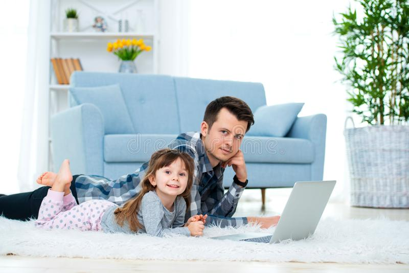 Cute little girl, daughter, sister and young dad father or brother look at the laptop monitor computer, lying on carpet on the. Cute little girl, daughter royalty free stock images
