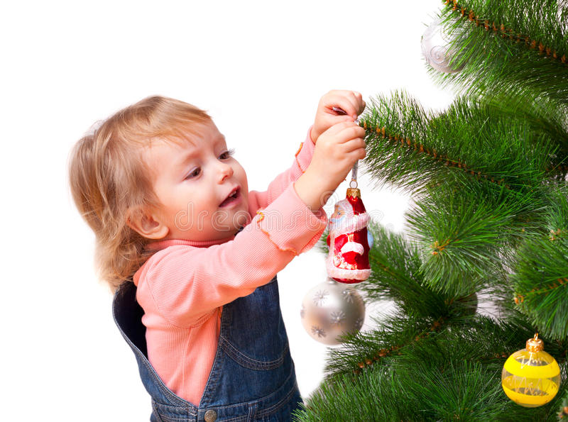 Cute little girl decorates the Christmas tree royalty free stock photo