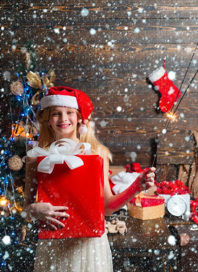 Cute little girl is decorating the Christmas tree indoors. Cute little girl teenager is decorating the Christmas tree stock image