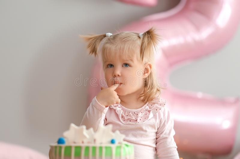 Cute little girl with delicious birthday cake sitting at home stock photography