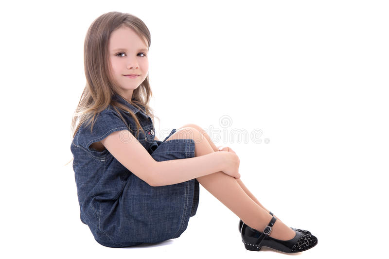Cute little girl in denim dress sitting isolated on white stock images