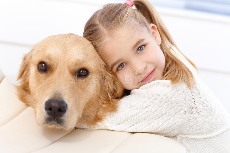 Cute little girl and dog embracing stock images