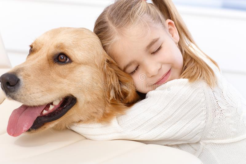 Cute little girl and dog embracing stock photo