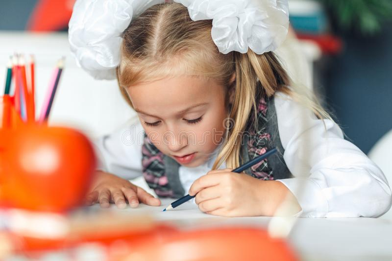 Cute little girl doing homework, closeup. Lovely schoolgirl drawing picture with colored pencils while sitting at table during art stock image