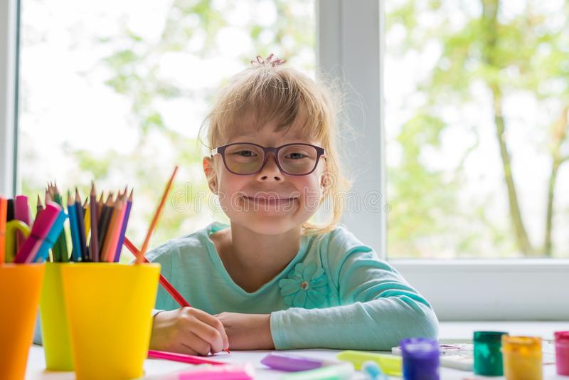 Cute little girl doing homework, reading a book, coloring pages, writing and painting. Children paint. Kids draw. Preschooler with stock photo