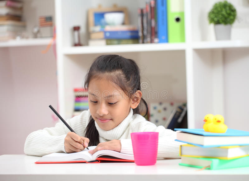 Cute little girl doing homework reading a book coloring pages writing and painting. Children paint. Kids draw. Preschooler with b royalty free stock photo