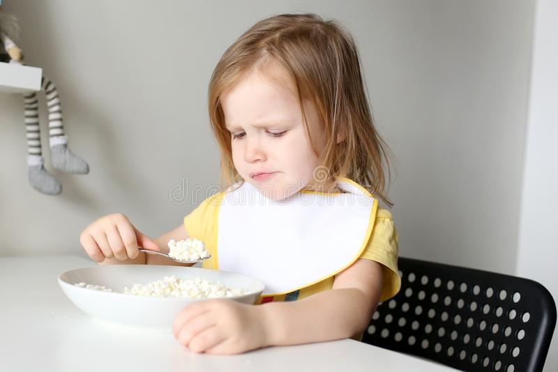 Cute little girl dont want to eat quark on kitchen royalty free stock photos