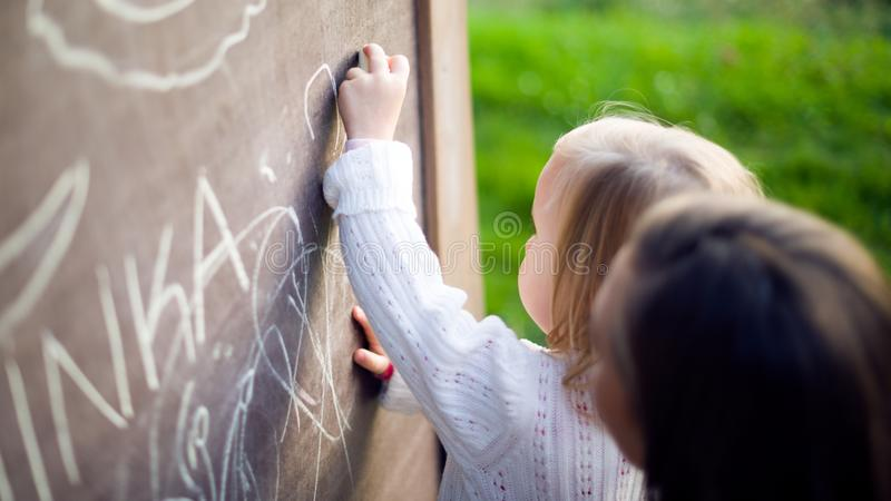Cute little girl drawing on blackboard. Toddler girl holding chalk and drawing. royalty free stock images